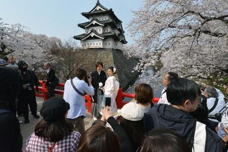 満開の桜と弘前城をバックに、下乗橋で記念写真を撮影した妹尾夫妻