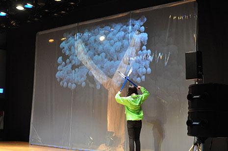 映像に映し出された桜の木を誤って切るシーン。会場からはどよめきも
